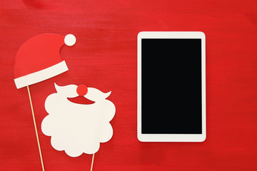On line christmas holiday shopping concept. Santa claus red and beard hat next to tablet device