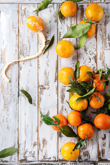 Ripe organic clementines or tangerines with leaves over white wooden plank table as background. Top view, space. Healthy eating