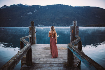 Rear view of young woman standing on pier at river