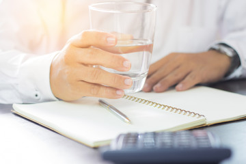 businessman holding glass of drinking water