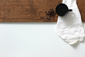 Coffee cup along with beans on wooden plank