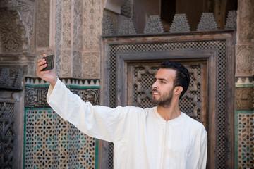 Arab man wearing traditional long white shirt taking selfie