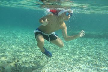Boy in Santa hat swimming in sea