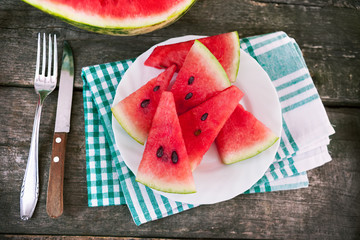 Watermelon slices with plate on cloth