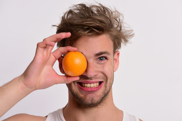 Man with orange covering one eye in his hand