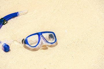 Diving mask and snorkel on sand beach