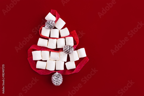 christmas tree shape made of marshmallows and ribbon sweets on deep red colored background flatlay