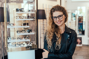 Portrait of smiling woman in optical store. Wall mural