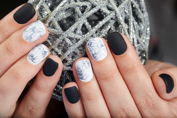 Hands with short manicured nails colored with black and white nail polish