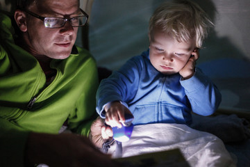 Father reading his son (2 years) from a book inside a tent, Haide, Ummanz, Island of Ruegen, Mecklenburg-Western Pomerania, Germany