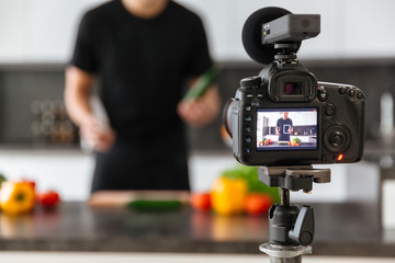 Close up of a video camera filming young male blogger