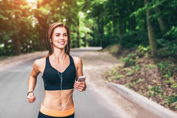 Young fitness girl running and listening music in the park