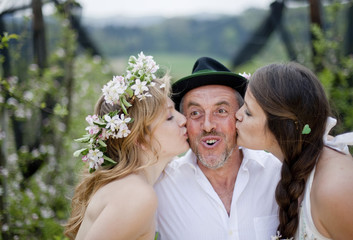 Two young women kissing a fruit farmer, Riegersburg, Styria, Austria
