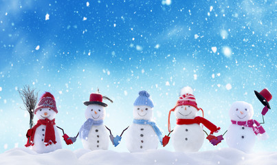 Wall Mural - Merry Christmas and happy New Year greeting card with copy-space.Many snowmen standing in winter Christmas landscape.Winter background