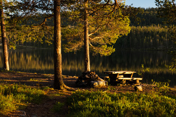 Picnic table by lake in evening light