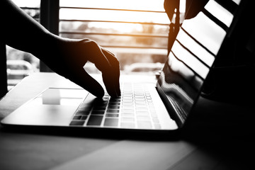 Fototapeta hands of anonymous hackers typing code on keyboard of laptop for remotely reach and receiving personal information online networking, Internet Crime Payment Security Concept, Silhouette black white