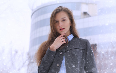 Young girl outdoors in winter. Model girl posing outdoors on a w
