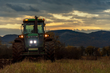 Farmer in tractor preparing land with cultivator.