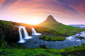 Picturesque icelandic landscape with colorful sunrise on Kirkjufellsfoss waterfall. Amazing morning scene near famous mountain - Kirkjufell volkano, Iceland, Europe