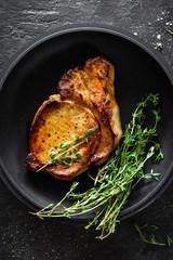 Pork meat, grilled steak on black background, top view