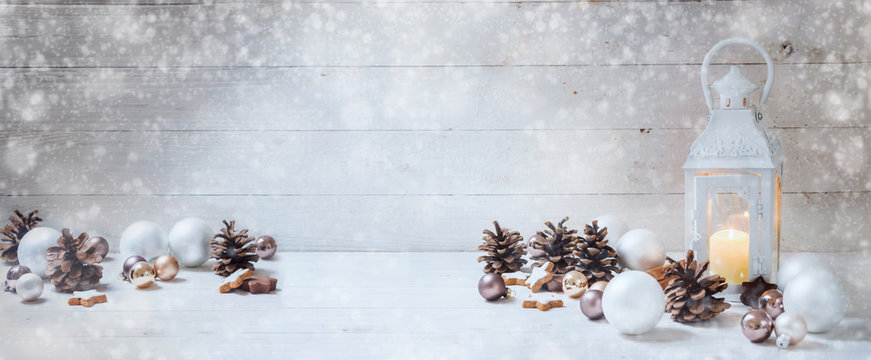 wide christmas background with a candle light lantern, baubles, cinnamon stars and cones on rustic white wood, panorama format for website banner, copy space