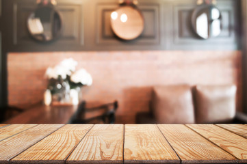 empty wooden table in front of blur coffee shop cafe or restaurant background