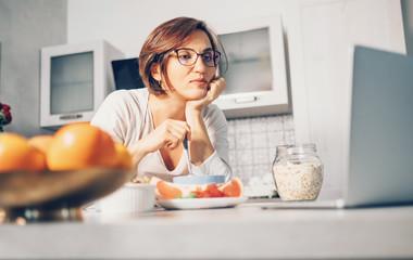 Woman prepare breakfast and watch laptop on kitchen