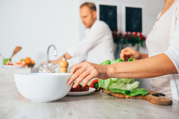 Couple on kitchen cooks together