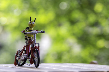 Bee dolls riding a bicycle on wooden ,background bokeh