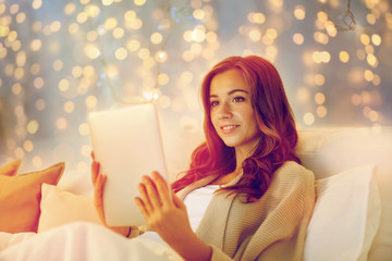 Fototapete - happy young woman with tablet pc in bed at home