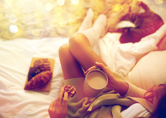 Fototapete - close up of woman with cocoa cup and cookie in bed
