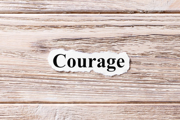 COURAGE of the word on paper. concept. Words of COURAGE on a wooden background