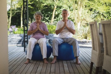 Full length of senior couple meditating together while sitting