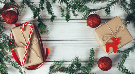 Christmas gifts in boxes of Kraft paper on a wooden table decorated with branches of Christmas tree