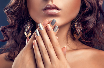 Beautiful woman with pink and silver manicure and perfect makeup