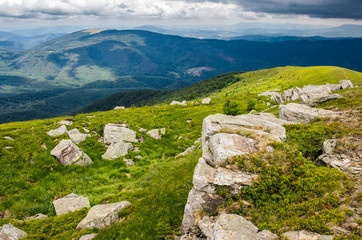 boulders on a green grassy slope of mountain ridge. beautiful summer landscape of Carpathians before the storm
