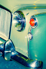 The front of a green classic, vintage car