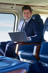 Portrait Of Businessman Working On Laptop In Helicopter Cabin During Flight