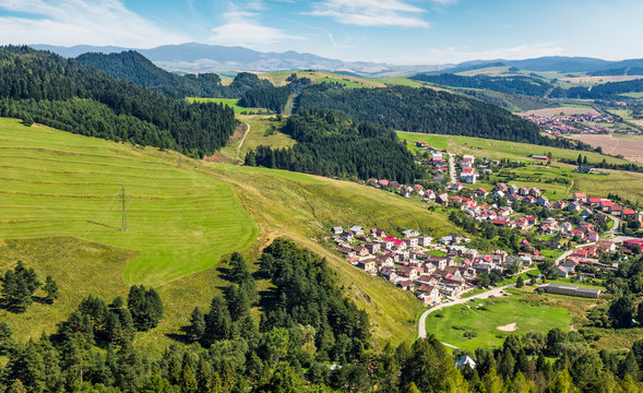 Slovakian town Stara Lubovna on grassy hillside. beautiful rural scenery in mountainous area viewed from above on a summer day.
