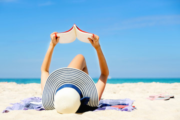 Young women lying on a tropical beach, relax with book. Blue sea in the background. Summer vacation concept.