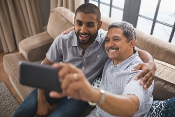 Happy man with his son taking selfie at home