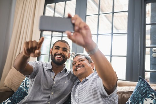 Smiling man with his father taking selfie at home