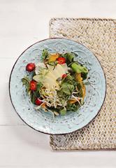 Piatto di insalata fresca con fragole, germogli, mela e carote su sfondo chiaro. Cucina vegetariana. Alimentazione sana