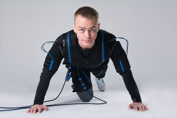 Man in an electric muscular suit for stimulation does the exercises