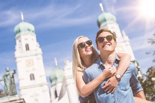 Junges Paar Huckepack am Domplatz in Passau an einem sonnigen Tag