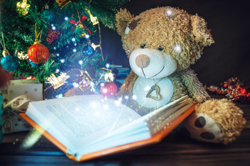 Teddy bear holding an open book with the light. Reading Christmas tales. Concept of new year's eve Magic