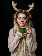 Portrait of pretty happy girl wearing deer costume. isolated black background
