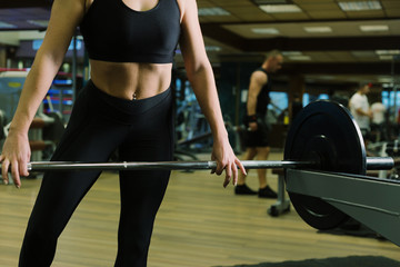 Close up - body sport woman. Sporty woman exercising with barbell in gym. Strong man with dumbbells in the background