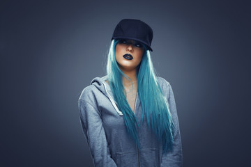 Young woman with cyan color hair in hoodie and cap