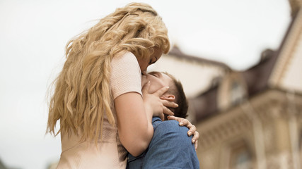 Boyfriend raising his girlfriend up and kissing her, passionate relationship